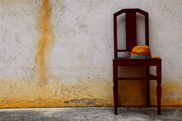 A lonely chair by a stained wall.